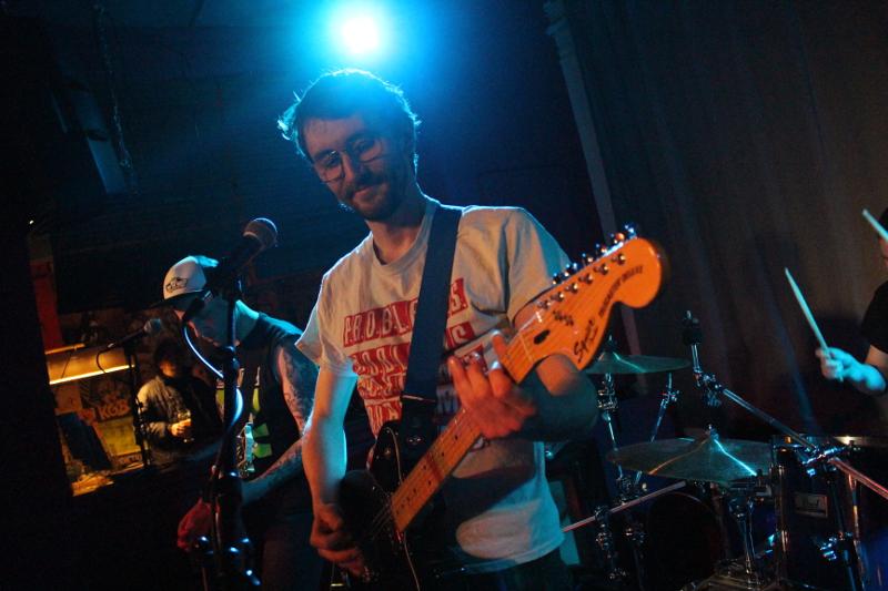 Sänger Johannes lächelt, Frank in das Gitarrenspiel vertieft