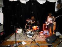 Männer zerstören Schlagzeug, Frau schaut zu.