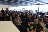 Raum ist gut gefüllt, Publikum wirkt skeptisch